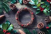 Making Christmas wreath using fresh and all natural materials. Christmas wreath with red berries and poster