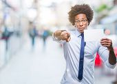 Afro american man holding blank card over isolated background pointing with finger to the camera and poster