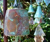 foto of windchime  - several wind chimes hanging outside garden with large one in front - JPG