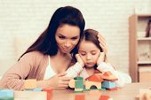 Mother Teaches Daughter. Educational Game. Learning Child At Home. Build House Of Cubes. Woman And S poster
