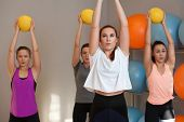 Sporty Young Women Training With Medicine Balls In Fitness Class. Group Exercise In Modern Fitness C poster