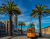 An Old Orange San Francisco Cable Car On The Embrcadero With The Ferry Building And Palm Trees In Th poster