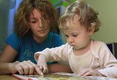 foto of girl reading book  - A mother is teaching her child with a book - JPG