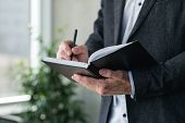 Man Hand Writing In Notepad. Agenda Or Scheduled Control Of Business Affairs. poster