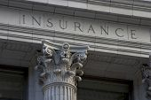 stock photo of insurance-policy  - neoclassical architechture sports a column with the word insurance above it - JPG