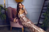 Luxury Long Party Dress With Shining Sparkles And Beautiful Fashion Design. Young Brunette Model Sit poster