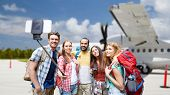 travel, tourism and people concept - group of smiling friends or tourists with backpacks taking pict poster