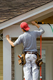 pic of soffit  - A construction worker on a ladder working on the wiring in the soffit of a house.
