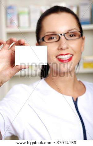 Female pharmacist with business card in pharmacy, focus on card