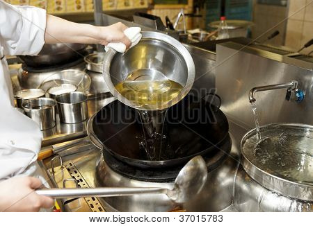 Chef is pouring cooking oil in wok an commercial kitchen