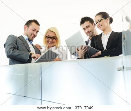 Young business people having conversation using laptops and tablets