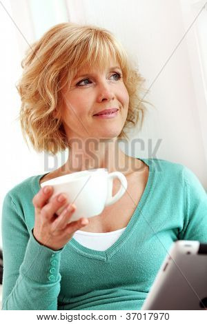 Middle age woman relaxing with tablet comper at home