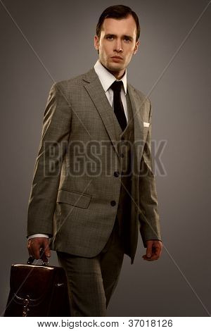 Businessman with a briefcase isolated on grey