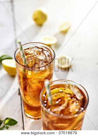 cold ice tea with sliced lemons and straws