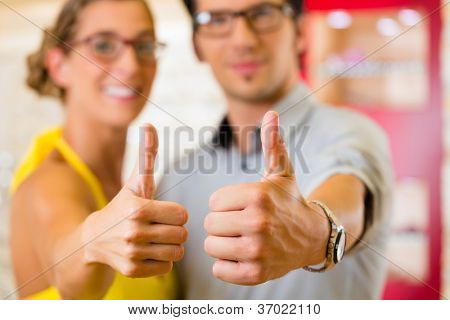 Young couple at optician in the store, they looking for glasses, thumps up