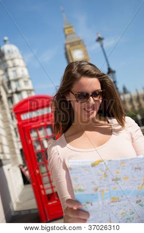 Woman walking as a tourist in London with a map