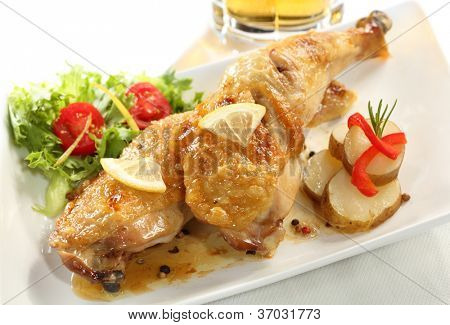 Dish of two roasted chicken legs isolated on white (left top), beer glass on background.