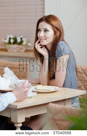 Lady talks with man sitting at the table at the restaurant