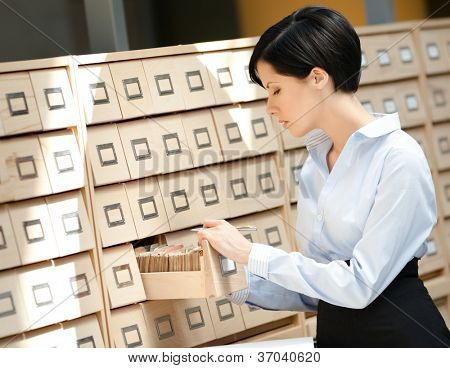Woman seeks something in card catalog composed of set of wood boxes at the library. Education and research