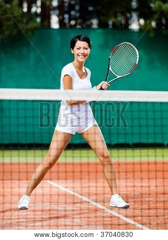 Sportswoman at the tennis court with racquet. Contest