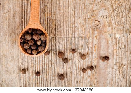 pimento in wooden spoon on rustic wooden background