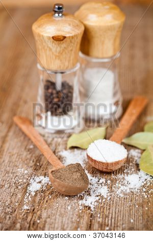 salt and pepper in spoons and shakers, bay leaves on rustic wooden table
