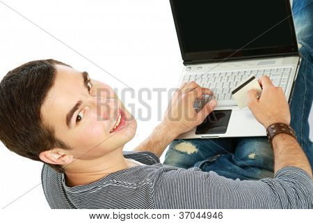 A young man sitting on the floor with a laptop, holding a credit card