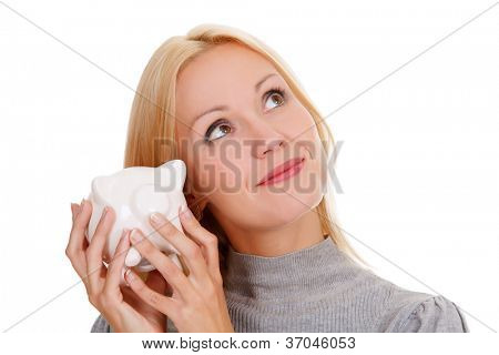 Smiling woman with piggy bank posing against white background