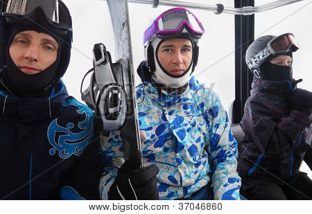 Three skiers in helmets ride on funicular in mountains. Focus on middle man.