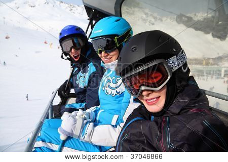 Three happy skiers in helmets and goggles ride on funicular in mountains. Focus on boy.