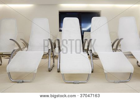 Two rows of white comfortable seats in empty room for waiting.