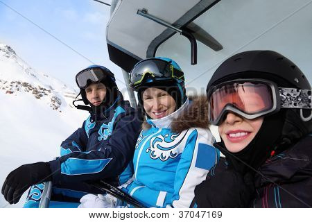 Three happy skiers in helmets and sport suits ride on funicular in mountains. Focus on woman.