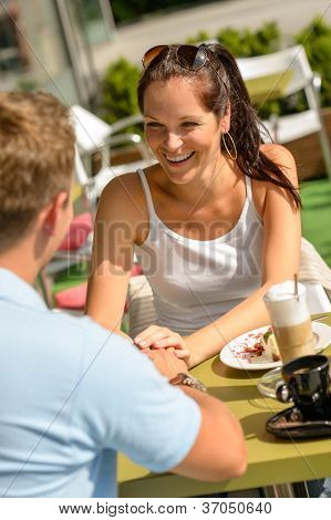 Couple flirting holding hands at cafe bar restaurant terrace sunny