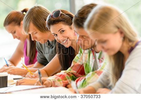Students writing at high-school exam teens study campus academic class