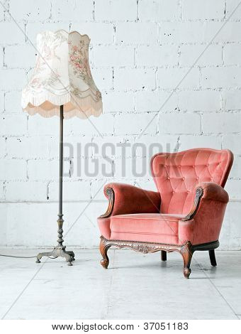Pink classical style Armchair sofa couch in vintage room with desk lamp