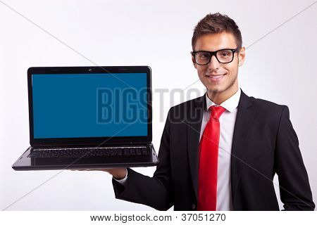 Confident business man or student in glasses holding a laptop