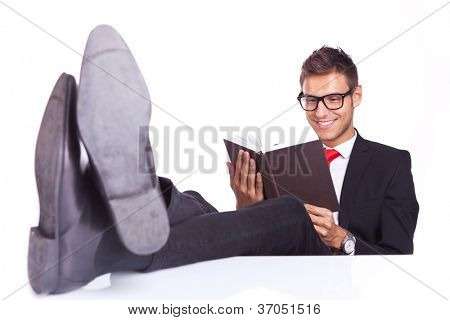 relaxed business reading a book with his feet on the desk top