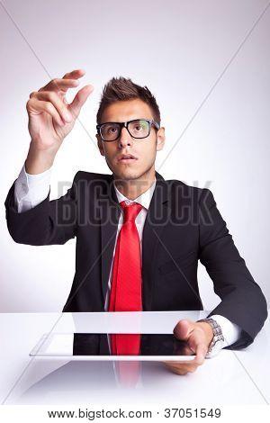 joven empresario recogiendo algo imaginario sobre su almohadilla táctil sobre fondo gris studio