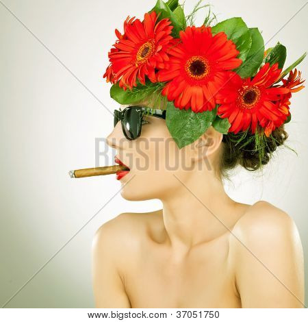 side view of a relaxed sexy woman with cigar in her mouth and wearing red gerbera flowers on her head - vintage picture style