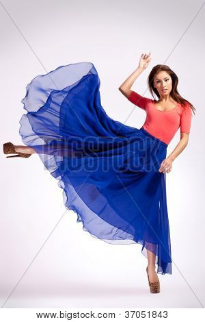 young woman in blue dress kicking to her side and looking at the camera