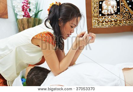 Traditional thai massage health care procedure, kneading back and shoulders muscules of man
