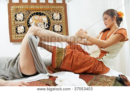 Traditional thai massage health care procedure, kneading foot and leg muscules of man