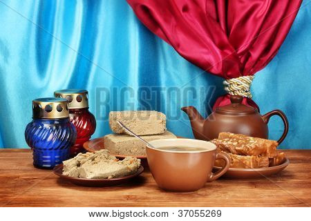 Teapot with cup and saucers with oriental sweets - sherbet and halva on wooden table on a background of curtain close-up