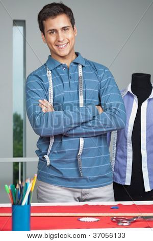 Portrait of young male tailor standing arms crossed by table with mannequin in background