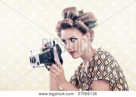 Woman holing vintage 4x6 film camera looking through viewfinder.