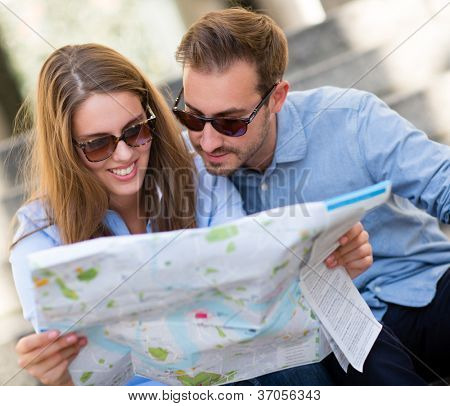 Happy couple of tourists looking at a map