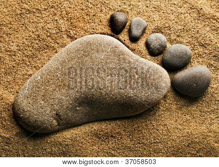 alone trace footprint of the feet made of a pebble stone on sea sand texture background