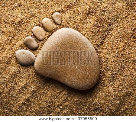 trace feet of a pebble stone  on the sea sand backdrop