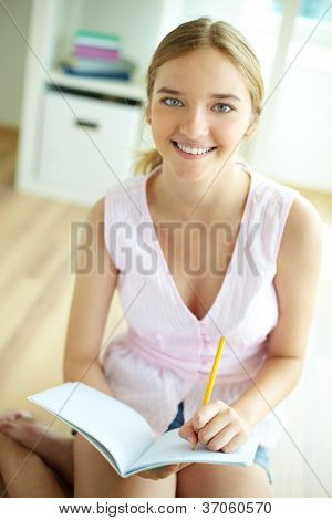 Pretty girl sitting on the floor and looking at camera while doing homework