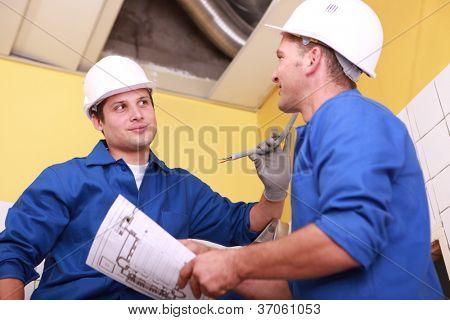 zwei Arbeiter in einem Haus im Bau in blauen Overalls gekleidet, nimmt eine davon eine Zeichnung